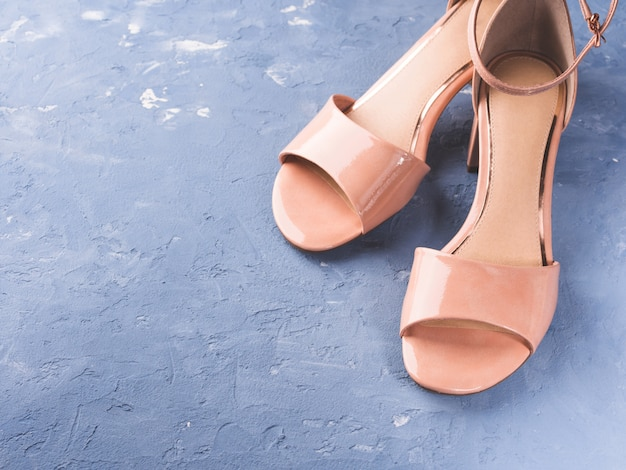 Pair of woman pink sandals on blue
