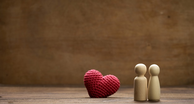 Pair of wooden men of the bride and groom, red heart, brown background, concept of love and relationships. copys pace