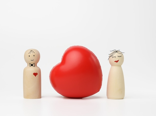Pair of wooden men of the bride and groom, between them a red heart, white background