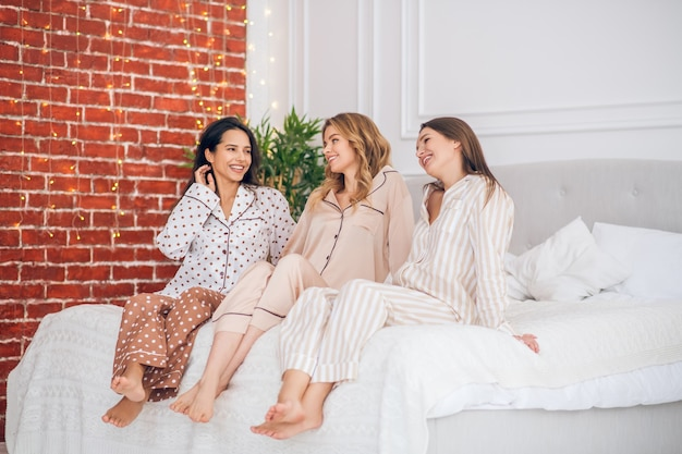 Pajama party. three cute girls spending time together while having pajama party