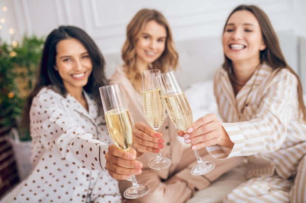 Pajama party. three pretty girls having pajama party and drinking champagne