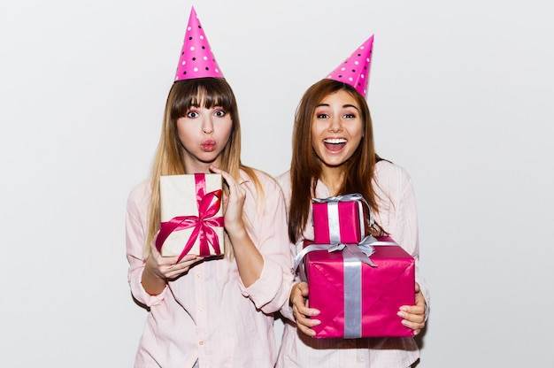 Pajamas birthday party. friends having fun and holding gift boxes. surprise face, exited emotions. girls wearing prop party hats. indoor.