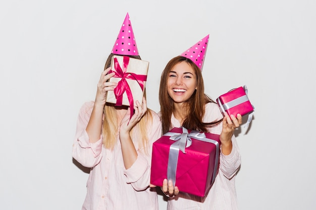 Pajamas birthday party. friends having fun and holding gift boxes. surprise face, exited emotions. girls wearing prop party hats.