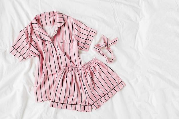 パジャマスリーピングキット。ベッドにストライプのクラシックなピンクのスリープドレス。おはようコンセプト。フラットレイ、上面図