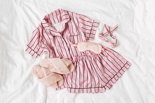 Pajamas sleeping kit with fluffy fur slippers. classic pink sleep dress with stripes in bed. good morning concept. flat lay, top view