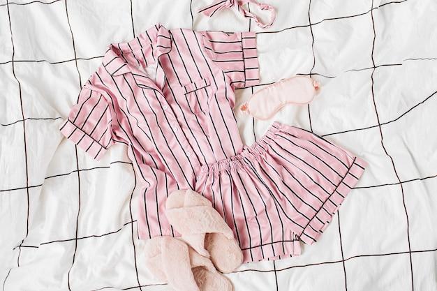 ふわふわの毛皮のスリッパが付いているパジャマの睡眠キット。ベッドにストライプのクラシックなピンクのスリープドレス。おはようコンセプト。フラットレイ、上面図