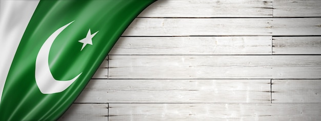 Pakistan flag on old white wall. horizontal panoramic banner.