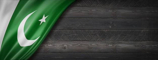 黒い木の壁にパキスタンの旗。水平方向のパノラマバナー。