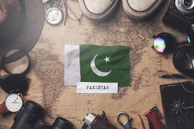 Pakistan flag between traveler's accessories on old vintage map. overhead shot