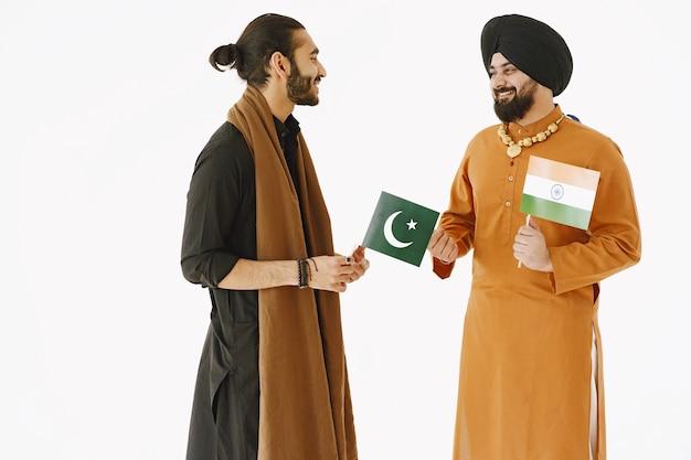 民族衣装を着たパキスタン人男性とインド人男性。友達は、孤立した白い背景で話しています。国同士の仲裁。