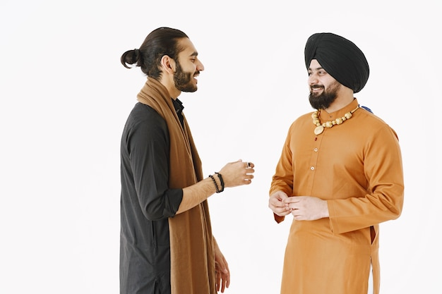 Pakistani man and indian men in traditional clothes. the friends are talking at white background, isolated. agremment between countries.
