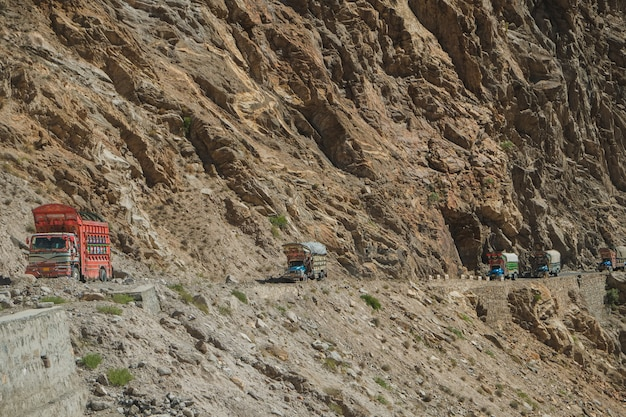 Pakistani trucks travelling on paved road along the mountain near the cliff in karakoram highway.