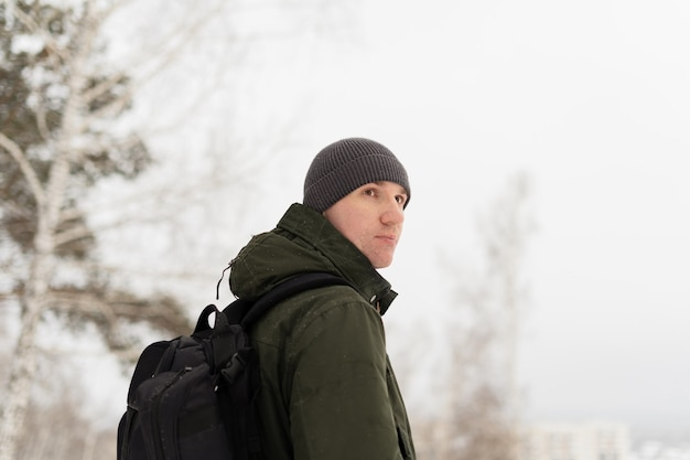 Pakren in a green jacket and with a backpack in winter landscape stands turning back
