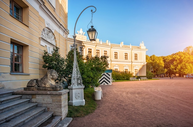 Palace in pavlovsk  in st. petersburg, lit by the autumn sun, a statue of a lion on the stairs and a lantern