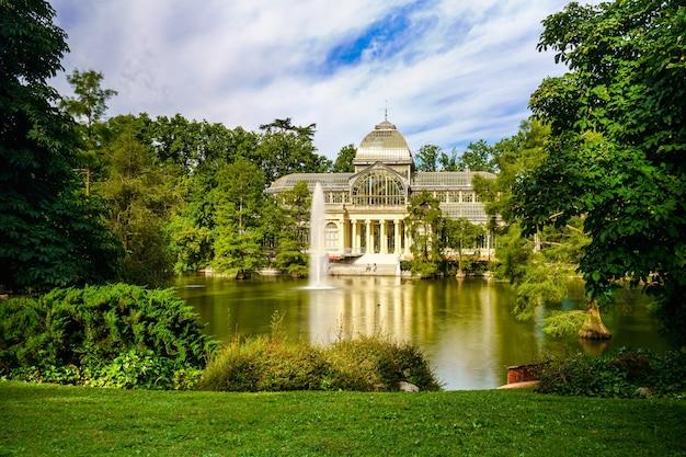 Паласио-де-кристал в мадридском общественном парке ретиро с озером на главном фасаде.