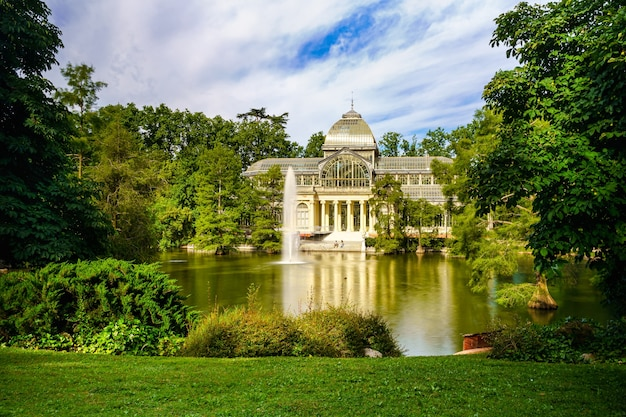 Palacio de cristal in madrid's retiro public park with its lake on the main faã§ade.