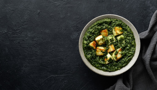 Palak paneer indian traditional food on black background, top view, copy space