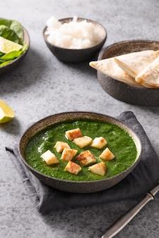ほうれん草のパニールと灰色の石の背景のインド料理のパニールチーズ