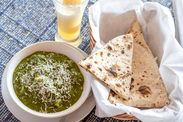 Палак панир или карри из шпината и творога - это здоровый рецепт основного блюда в индии. популярный индийский здоровый обед, меню ужина, подается с роти или чапати