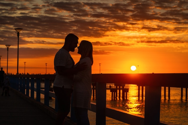 Palanga, lithuania. silhouettes of a couple in love stand on a wooden pier by the sea at sunset