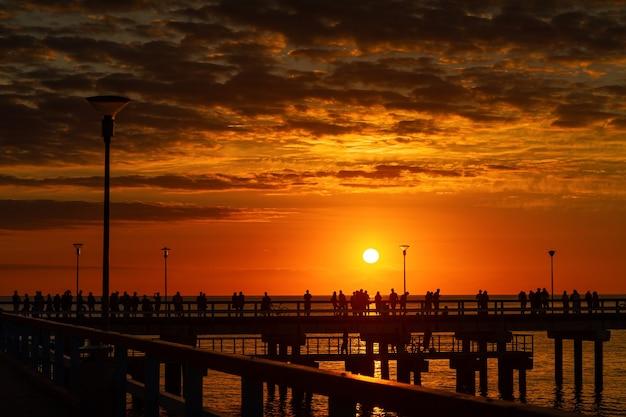 リトアニア、パランガ。日没時の海沿いにたくさんの人が集まる木製の桟橋