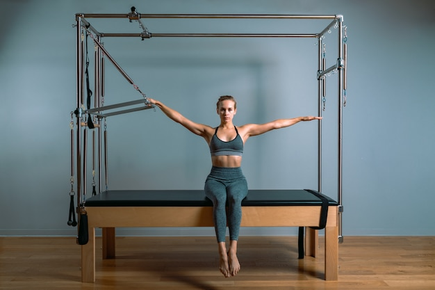 Palates trainer girl posing for a reformer in the gym. fitness concept, special fitness equipment, healthy lifestyle, plastic. copy space, sport banner for advertising.