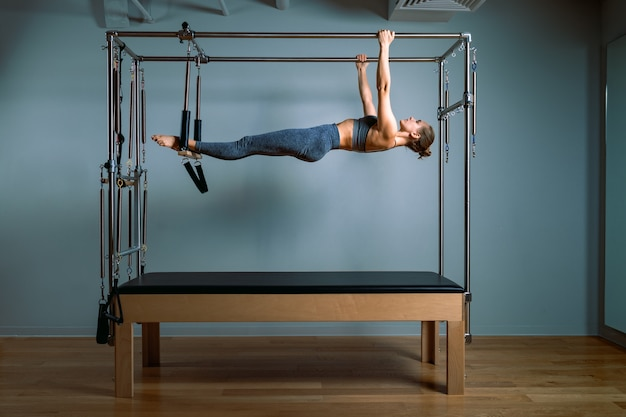 Palates trainer girl posing for a reformer in the gym. fitness concept, special fitness equipment, healthy lifestyle, plastic