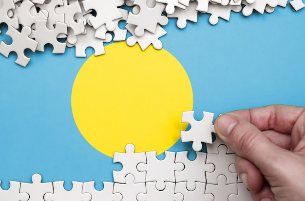Palau flag  is depicted on a table on which the human hand folds a puzzle of white color