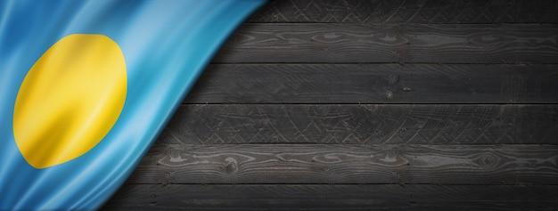 검은 나무 벽에 팔라우 플래그입니다. 수평 파노라마 배너.