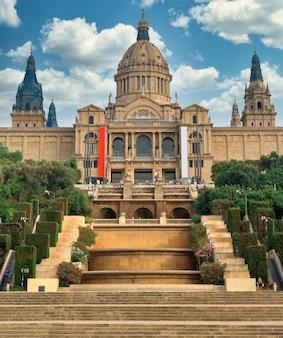 Il palau national di barcellona, in spagna, giardini e persone di fronte ad esso. cielo nuvoloso