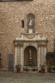 팔라초 마르티넨고 체사레스코 노바리노 궁전. 초라한 벽에 아름다운 동상과 석조 장식이 있는 작은 분수가 있는 안뜰. 냄비에 작은 분수와 식물과 꽃이 있는 오래된 조각.