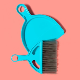 A pale blue dustpan and brush lying on living coral background
