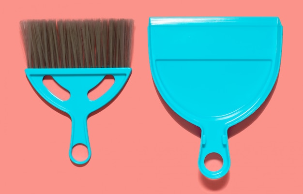 A pale blue dustpan and brush lying on living coral color. top view.