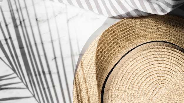 Pale brown hat and a striped grey and white cloth on a white background covered by a leaf shadow