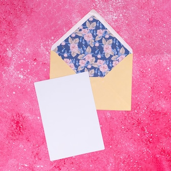 Pale colored envelope on pink marble background