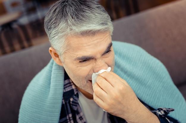 淡い顔。鼻水に苦しんでいる病気の暗い男の肖像画