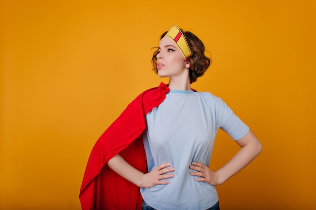 Pale girl in superhero costume looking away with serious face expression