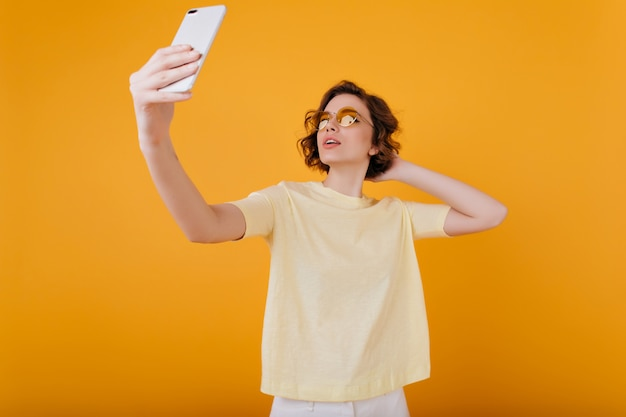 Pale girl with arm tattoo taking picture of herself in yellow room