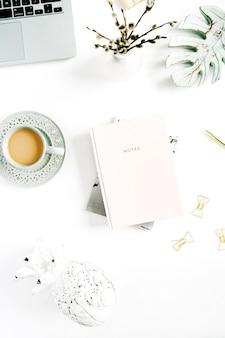 淡いパステル調のホーム オフィス デスク。ラップトップ、ピンクのノート、コーヒー、白い背景の装飾。平置き