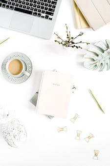 淡いパステル調のホーム オフィス デスクで、ノート パソコン、ピンクのノート、白い背景に装飾が施されています。フラットレイ、トップビュー