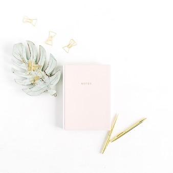 창백한 파스텔 핑크 노트북, 황금 펜 및 클립, 흰색 배경에 monstera 팜 리프 장식. 평면 위치, 평면도