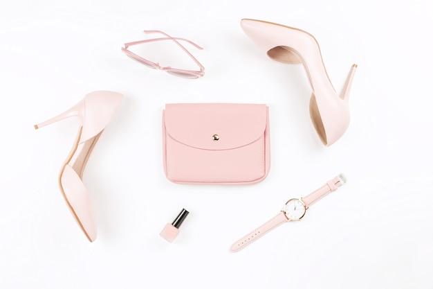 Бледно-розовые женские туфли и модные аксессуары на белом фоне