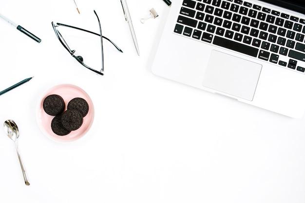 Бледно-розовый стильный домашний офисный рабочий стол с ноутбуком, кофе, очками и офисными принадлежностями на белой поверхности