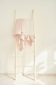 Pale pink waffle towels hang from a wooden staircase unusual home decor