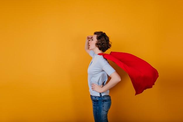 Pale short-haired girl wears red cloak havig fun in carnival
