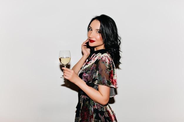 シャンパングラスを持って笑顔の黒髪の淡い女性