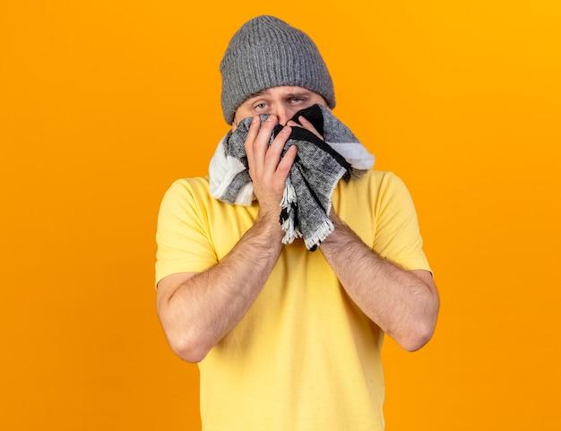 冬の帽子をかぶって、コピースペースでオレンジ色の壁に隔離されたスカーフを保持している淡い若い金髪の病気のスラブ人