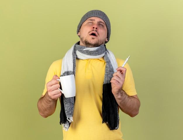 冬の帽子とスカーフを身に着けている淡い若い金髪の病気のスラブ人は、コピースペースでオリーブグリーンの壁に分離されたカップと温度計を保持します