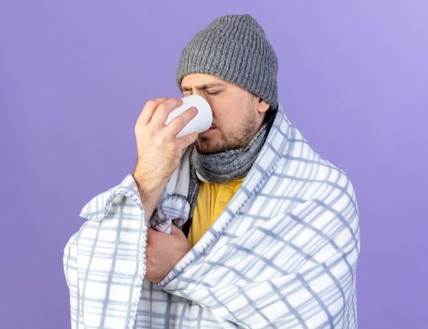 コピースペースと紫色の壁に分離されたカップから格子縞の飲み物に包まれた冬の帽子とスカーフを身に着けている淡い若い金髪の病気のスラブ人