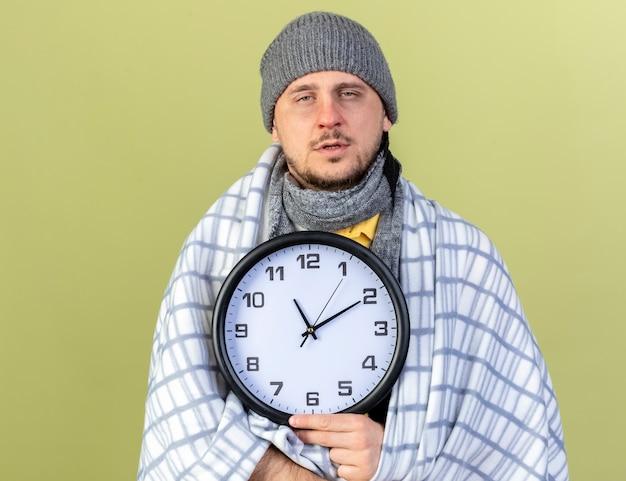 格子縞に包まれた冬の帽子とスカーフを身に着けている淡い若いブロンドの病気のスラブ人は、コピースペースでオリーブグリーンの壁に隔離された時計を保持します